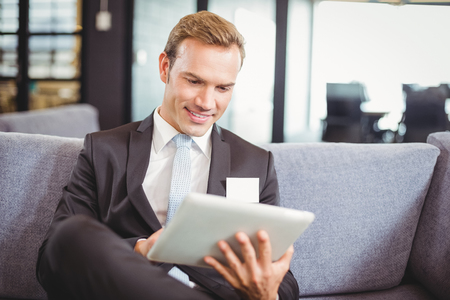 well read: Happy businessman sitting on sofa and using digital tablet in office