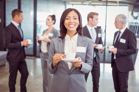 Retrato de negocios tomando el té durante el tiempo de descanso y su equipo interactuar en el fondo