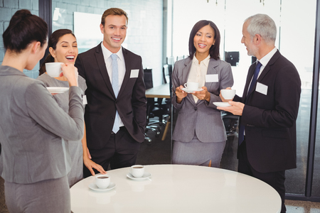interacting: Businesspeople having tea and interacting during breaktime in office