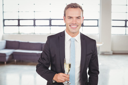 champagne flute: Portrait of young businessman holding champagne flute in the office