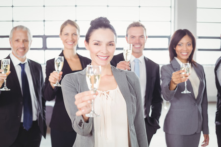 champagne flute: Portrait of business team holding champagne flute in the office Stock Photo