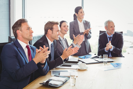 applauding: Businesspeople applauding in conference room during meeting