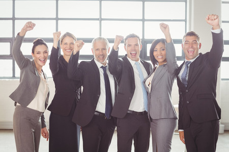 fist clenched: Team of businesspeople cheering with clenched fist in the office Stock Photo