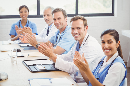 Portrait of medical team applauding in conference room