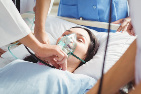 oxygen mask: Doctor putting an oxygen mask on patient in hospital