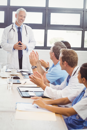 Los médicos aplaudiendo un compañero médico para su discurso en la sala de conferencias