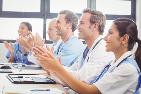 Medical team applauding in conference room in hospital