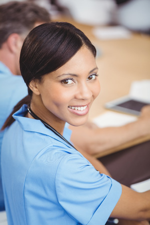health professional: Portrait of happy female doctor sitting on conference room in hospital Stock Photo