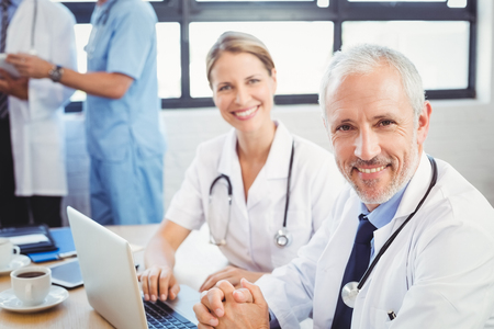 doctors smiling: Portrait of two doctors smiling in conference room in hospital
