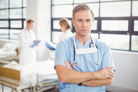 hands work: Portrait of doctor standing with arms crossed in hospital Stock Photo