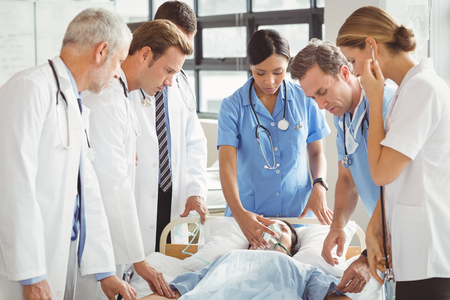 to examine: Doctors examine female patient in hospital