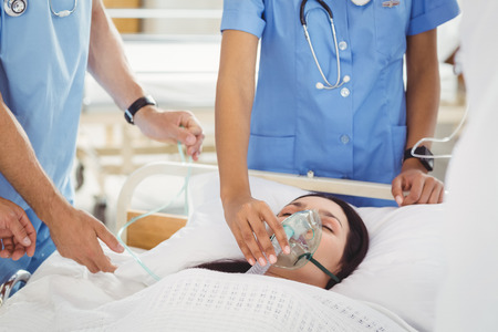 oxygen mask: Doctors putting an oxygen mask on patient in hospital