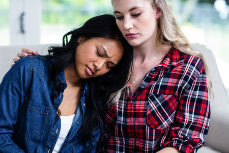 consoling: Close-up of woman consoling depressed female friend at home