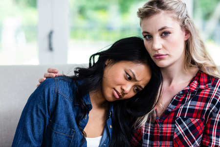 consoling: Close-up of young woman consoling upset female friend at home Stock Photo
