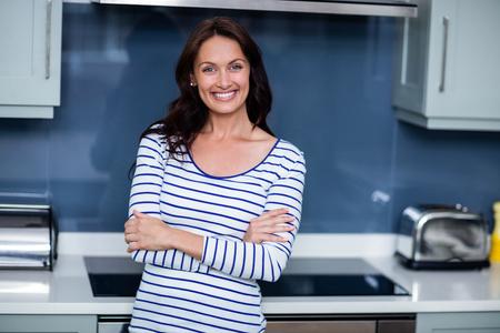 腕を組んでキッチンに立っている間幸せな若い女の肖像