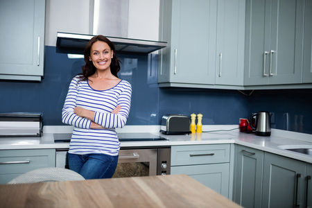 classy house: Portrait of smiling young woman with arms crossed while standing in kitchen Stock Photo