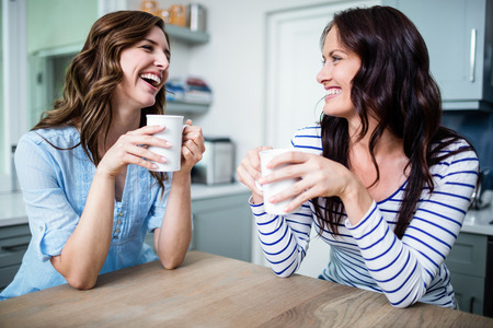 classy woman: Happy female friends holding coffee mugs while discussing at table in kitchen
