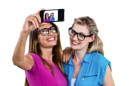 self   portrait: Smiling female friends taking self portrait while standing on white background