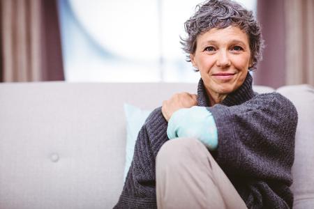 Portrét usmívající se dospělá žena sedí na pohovce doma Reklamní fotografie