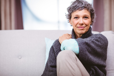 mature female: Portrait of smiling mature woman sitting on sofa at home Stock Photo