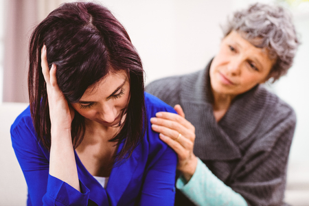 Mother comforting sad daughter sitting on sofa at home