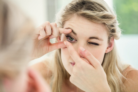 routing: Young woman applying contact lens while looking in mirror Stock Photo