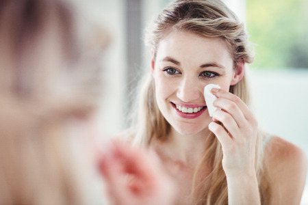 classy woman: Happy young woman applying blush while looking in mirror