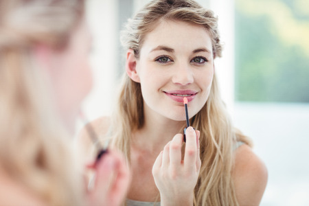 gloss: Portrait of smiling young woman applying lip gloss while looking in mirror