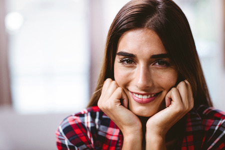 classy house: Close-up portrait of smiling young woman with hands on chin