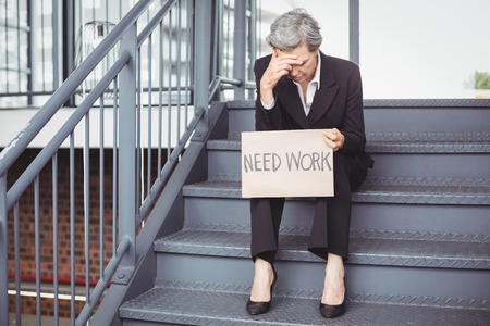 unemployment: Unemployed businesswoman holding need work placard while sitting on steps Stock Photo