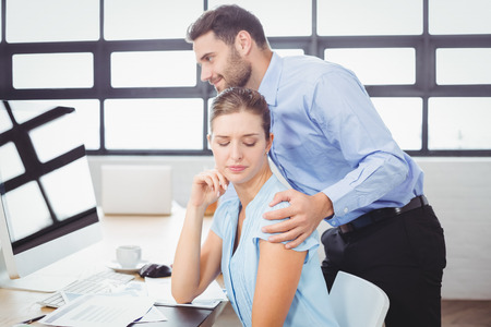 harassing: Businessman harassing female colleague at computer desk in office