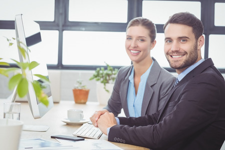 Portrait of happy business people working at computer at desk in office