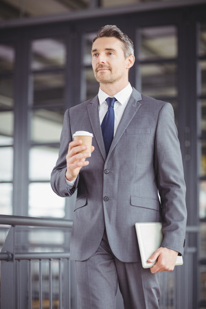 businesswear: Low angle view of businessman walking while holding disposable cup and digital tablet Stock Photo