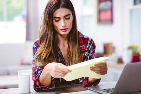 tensed: Tensed young woman looking at document while sitting at table