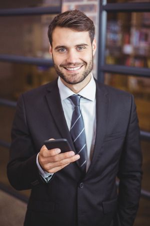 businesswear: Portrait of happy businessman using cellphone in office