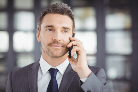 businesswear: Close-up of handsome businessman talking on cellphone in office