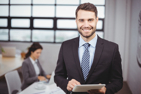 person standing: Portrait of confident young businessman using digital tablet while colleague in background