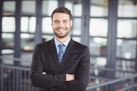 people attitude: Portrait of happy businessman with arms crossed standing in office Stock Photo