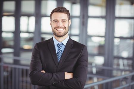 actitud: Retrato de hombre de negocios feliz con los brazos cruzados de pie en la oficina Foto de archivo