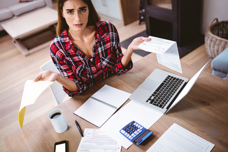 tensed: Portrait of tensed woman showing documents while sitting at table Stock Photo