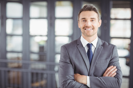 businesswear: Portrait of smiling businessman with arms crossed standing in office Stock Photo