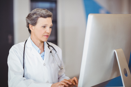 working on computer: Doctor working at computer desk in hospital Stock Photo