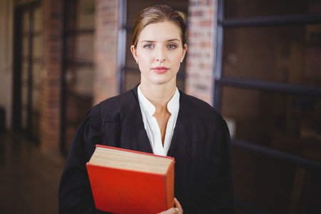 female lawyer: Portrait of confident female lawyer with book standing in office Stock Photo