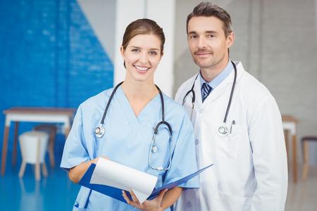 medical man: Happy doctors holding clipboard while examining at hospital