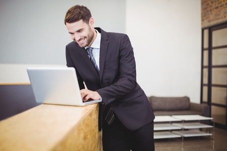 businesswear: Happy businessman using laptop while leaning on counter at office