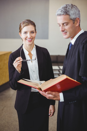 female lawyer: Happy female lawyer standing by male colleague in office