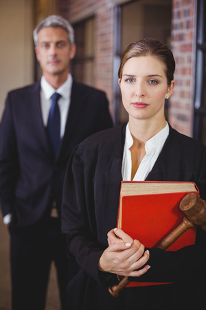 female lawyer: Portrait of female lawyer with male colleague standing in background Stock Photo