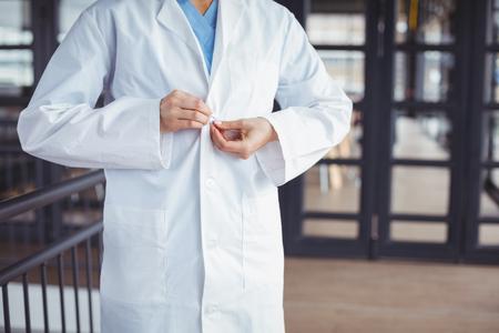 Sección media de médico con bata de laboratorio mientras está de pie en el hospital