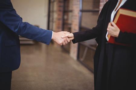 Midsection női ügyvéd kézfogás kliens állva hivatalban