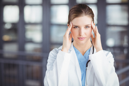 tensed: Portrait of tensed female doctor with head in hands while standing in hospital